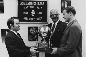 "Bill Musselman (right) accepts a trophy during his legendary run as head coach at Ashland College (now known as Ashland University), which saw his teams compile an incredible .845 winning percentage (109-20) from 1965-71. His teams reached the NCAA ""College"" Tournament four times, highlighted by a 1968-69 squad that allowed an NCAA record-low 33.9 points a game. The 1958 Wooster High graduate had a roller-coaster career that saw him coach 13 teams in 35 years, including the Cleveland Cavaliers, before passing away at age 59 in 2000."